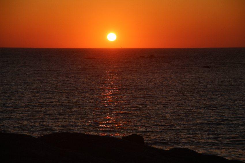 Gelber Sonnenball vor orange-rotem Himmel knapp über der Wasserlinie