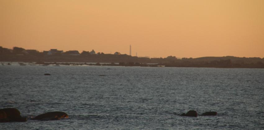 Blick auf den Phare de l'ile Vierge in der Ferne im orangenen Licht des Sonnenuntergangs