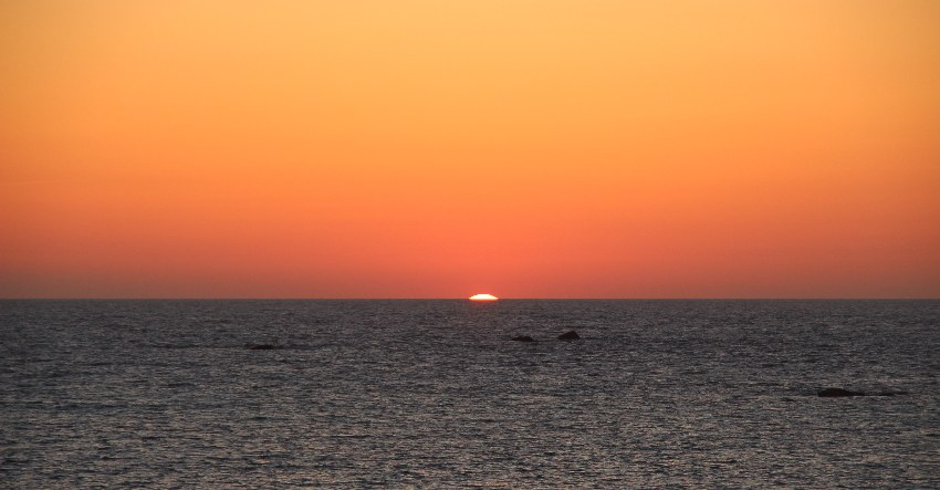 Himmel in allen Farben von gelb über orange zu rosa und rot als nur noch ein kleiner Punkt der Sonne über der Wasserlinie des ruhigen dunkelblauen Meers zu sehen ist