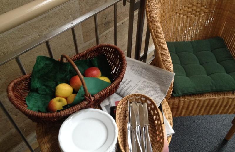 Äpfel in einem Holzkorb, dazu Teller und Messer und die Zeitung vom Tag auf einem Tischchen mit einem Bastsessel