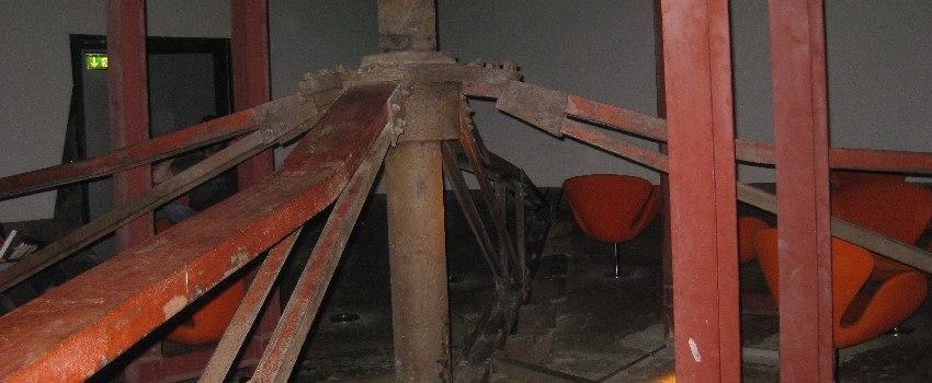 """Senkrechtes Rohr mit strahlenförmig davon ausgehenden Stüzpfeilern im """"Kinosaal"""" der Zeche Zollverein"""