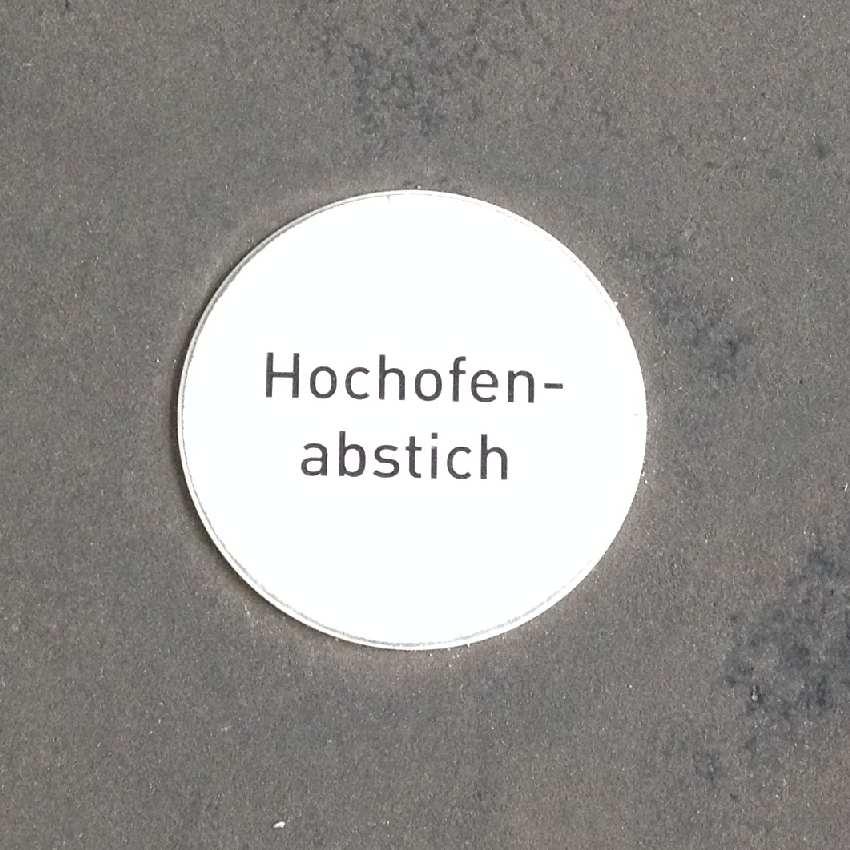 """Kleine runde Platte im Boden mit dem Text """"Hochofenabstich"""". Beim Betreten der Platte erklingt das entsprechende Geräusch"""