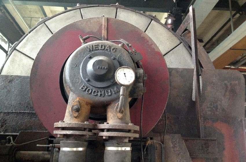 Großes rotes Rad mit einem Messgerät davor in der Zeche Zollverein in Essen