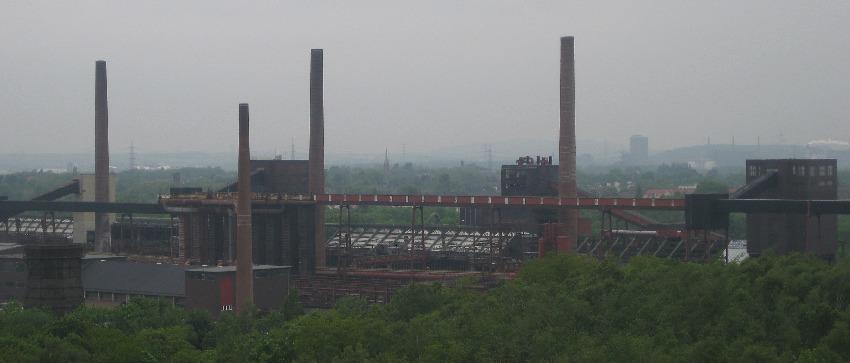 Blick über das Zechengeländer der Zeche Zollverein mit drei hohen Schornsteinen