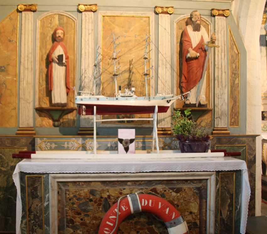 Linker Seitenaltar mit zwei Heiligenfiguren, einem Boot und einem modernen Rettungsring
