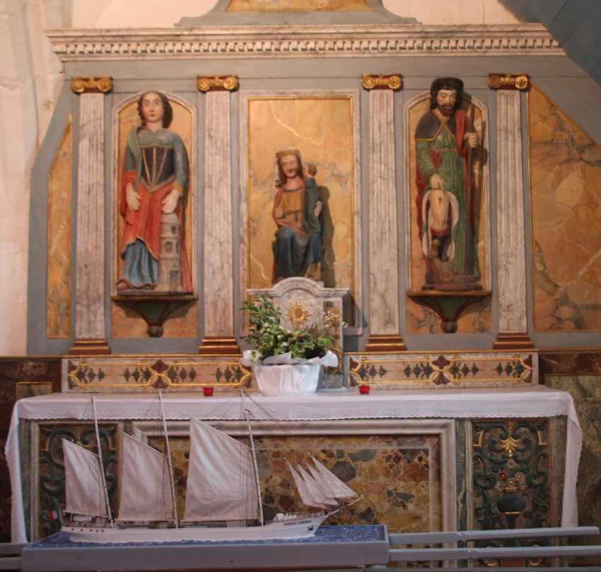 Rechter Seitenaltar der Chapelle Saint-They mit Muttergottes-Statue (in der Mitte), zwei weiteren Heiligen und einem selbstgebauten Segelboot