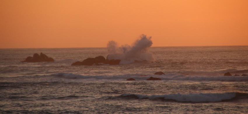 Wellen brechen sich bei Flut an einem Felsen und spritzen vor dem vom Sonnenuntergang rosa gefärbten Himmel meterhoch