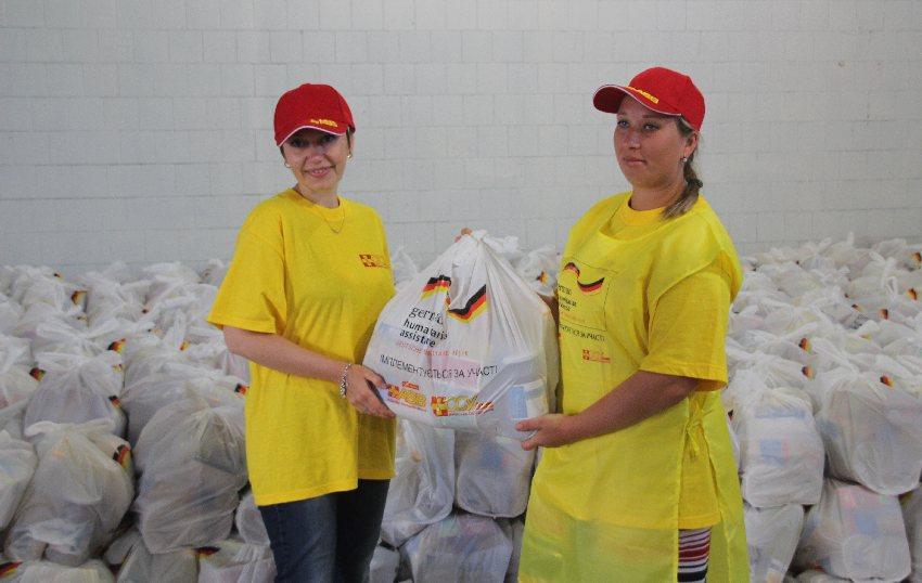 Zwei Helferinnen des Kiewer Samariterbundes mit einer Tüte volle Hilfsgüter