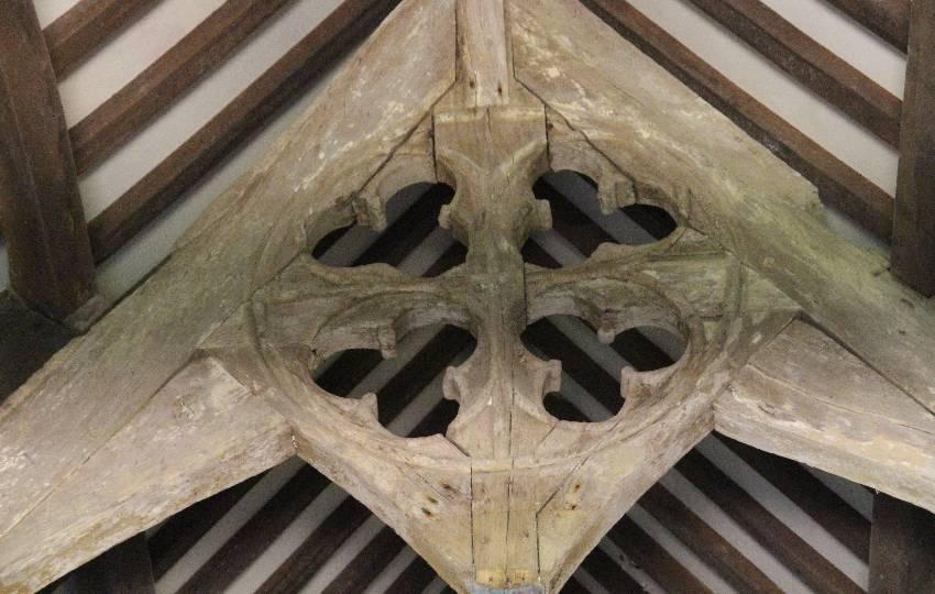 Holzbalken unter der Decke der Chapelle Notre-Dame de Penhors mit viel kleeblattförnigen Aussparungen als Verzierung