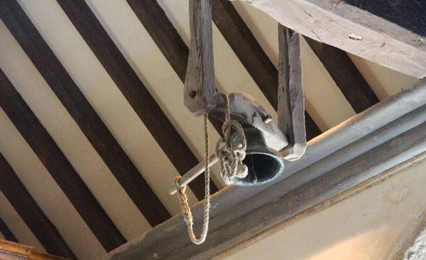Glocke an einem Holzbalken unter dem Dach der Chapelle Notre-Dame de Penhors in Pouldreuzic