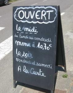 """Schiefertafel am Straßenrand, die darauf hinweist, dass geöffnet ist (""""Ouvert le midi"""")"""