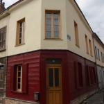 Gelb-rotes Eckhaus mit Holzfassade in Amiens