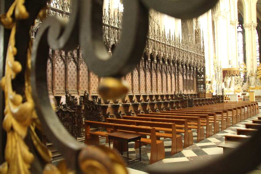 Blick durch die gusseiserne und teilweise vergoldete Chorschranke auf das historische Chorgestühl in der Kathedrale von Amiens
