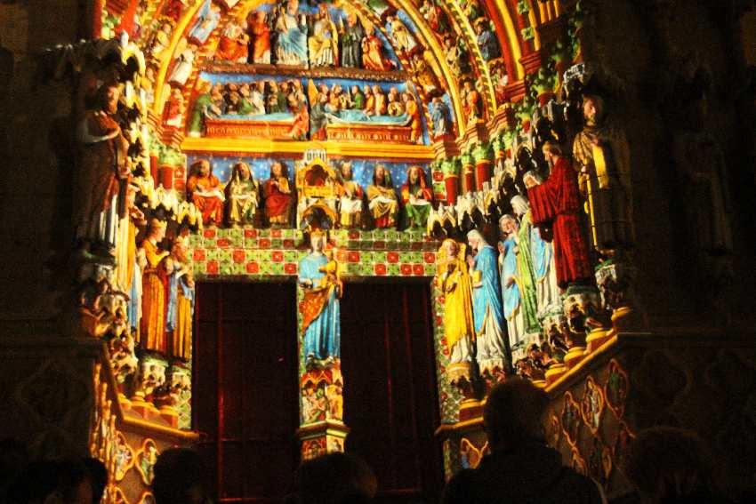 Durch Licht bunt eingefärbte Figuren und Statuen an der Kathedrale von Amiens - Detailaufnahme
