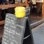 Restaurantwerbetafel, auf der ein gelber Muschel-Kochtopf befestigt ist, um darauf hinzuweisen, dass es hier Muscheln und Pommes frites gibt