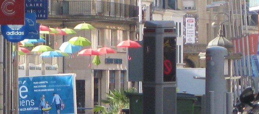 Bunte Sonnenschirme hängen in der Luft und werben für den Stadtstrand von Amiens
