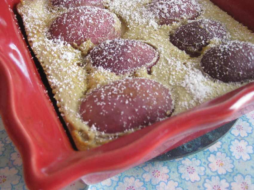Rand der Auflaufform mit etwas Clafoutis, Pfirsichen und Puderzucker
