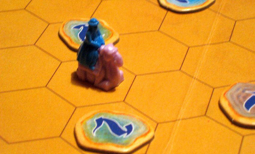 """Rosa Kamelfigur mit blauem Reiter auf dem sandfarbenen Spielplan von """"Durch die Wüste"""""""
