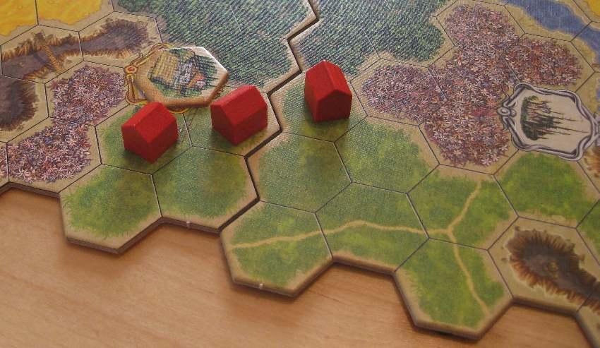 Drei kleine rote Häuser auf einem Wiesenfeld von Kingdom Builder