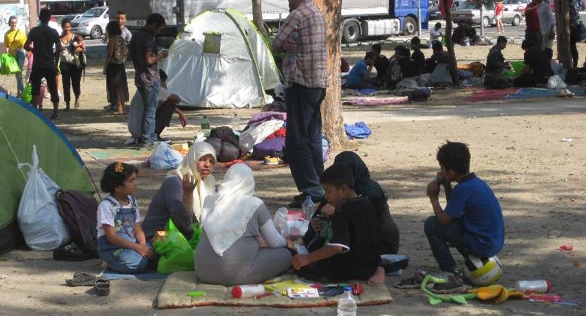 Flüchtlingsfamilie, die im Zentrum von Belgrad in einem Park unter einem Baum im Schatten auf dem Boden sitzt