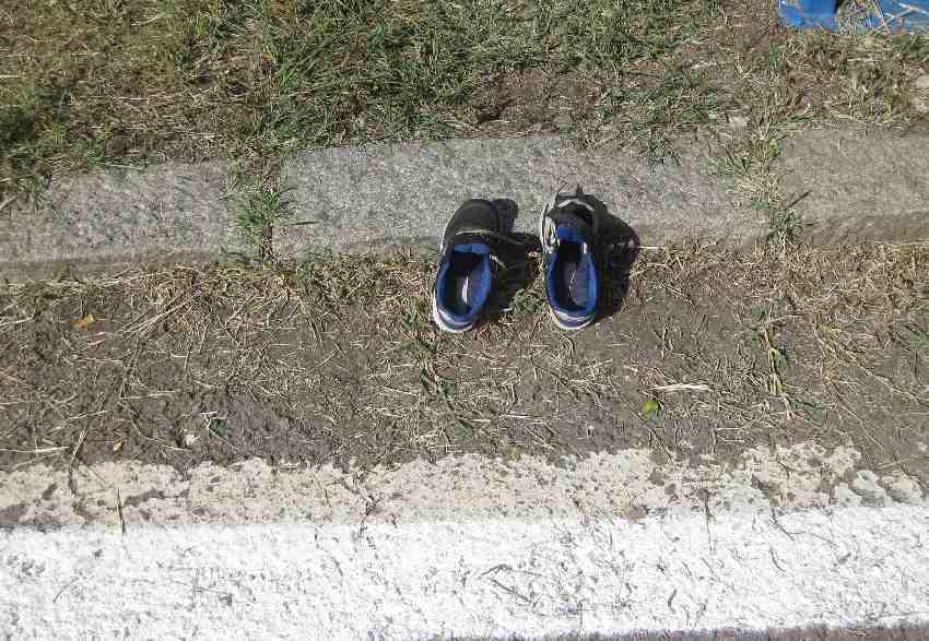 ein paar verlassene Kinderschuhe am Straßenrand