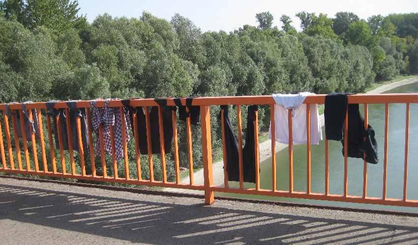 am Brückengeländer zum Trocknen festgebundene Hosen