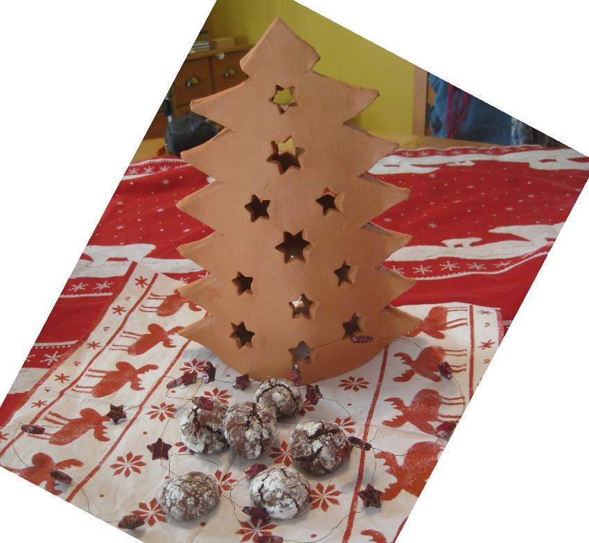 Schokoladen-Crincle-Plaetzchen vor einem Ton-Weihnachtsbaum