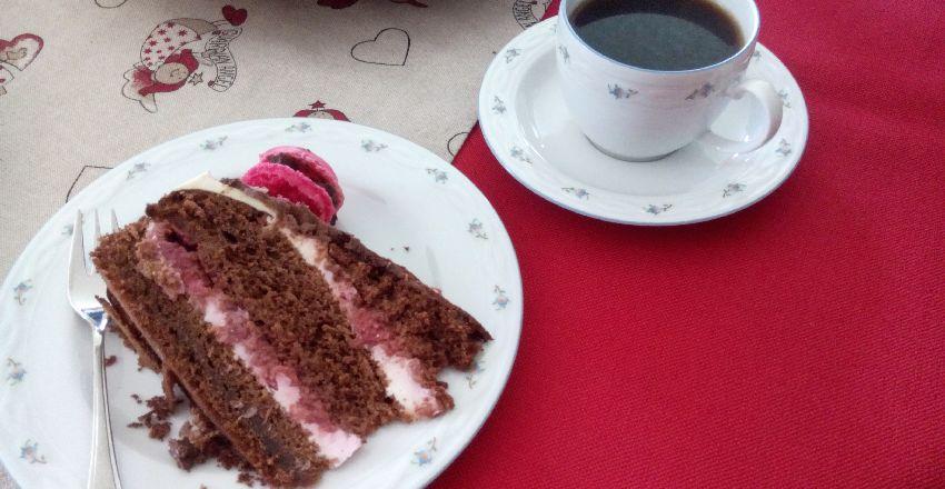 Stück der Schoko-Himbeer-Torte auf einem Teller mit einer Tasse Kaffee