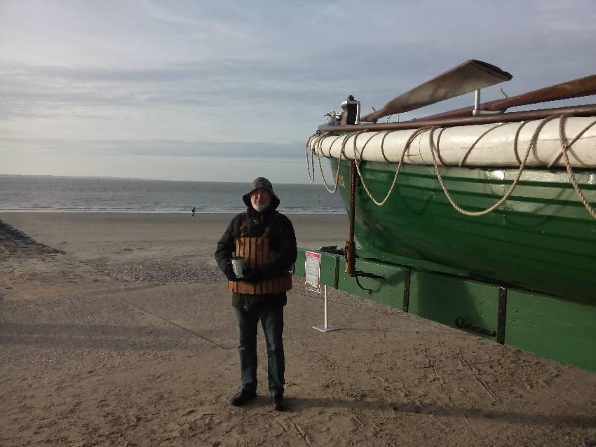 Seenotretter mit historischer Schwimmweste vor Rettungskutter
