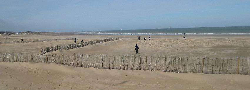 Strand von Calais mit Holzzaun und Fußgängern im Sonnenschein