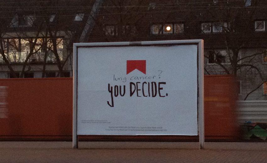 """Werbeplakat mit """"you decide"""" und von Hand hinzugefügter Frage: lung cancer?"""