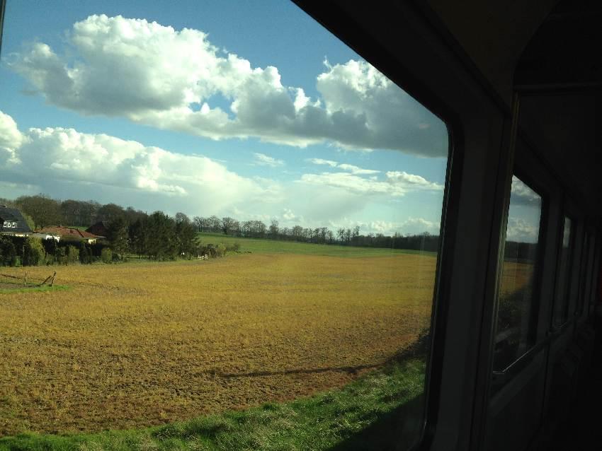 Blick aus dem Zugfenster auf ein noch unbestelltes Feld