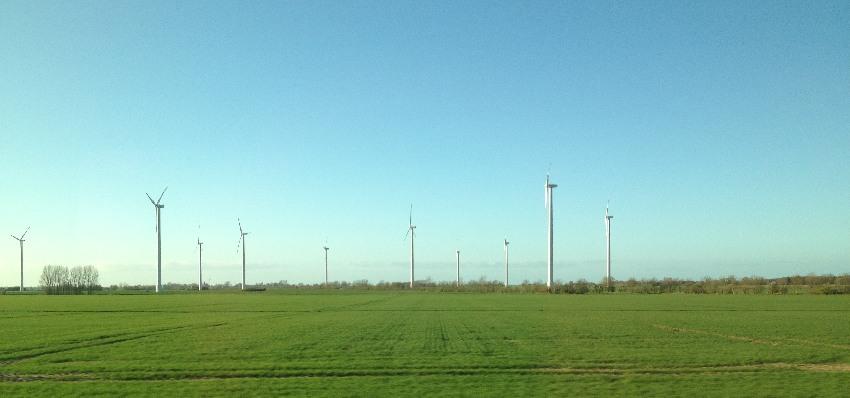Windräder auf einer Wiese in Mecklenburg-Vorpommern an der Bahnstrecke zwischen Schwerin und Stralsund