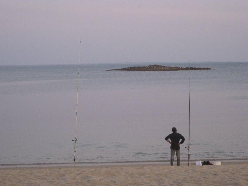 Angler am ansonsten leeren Strand