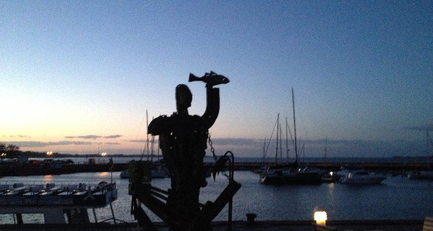 Stralsund: Statue mit Fisch und Fischerboote auf dem Strelasund im Abendrot