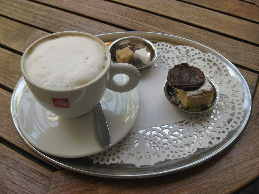 Kaffeegedeck mit Cappucino und einem kleinen Stück Kuchen sowie einer kleinen blumenförmigen Schokolade