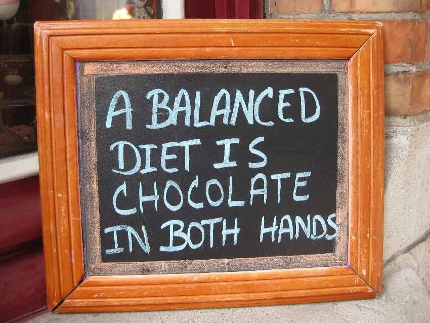 Schild mit der handgeschriebenen Aufschrift: A balanced diet is chocolate in both hands.