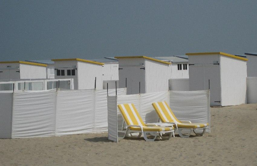 Strandliegen vor weißen Strandhäuschen an der flämischen Küste in Belgien