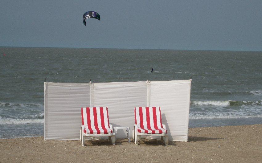rot-weiß-gestriefte Strandliegen und ein weißer Windschutz