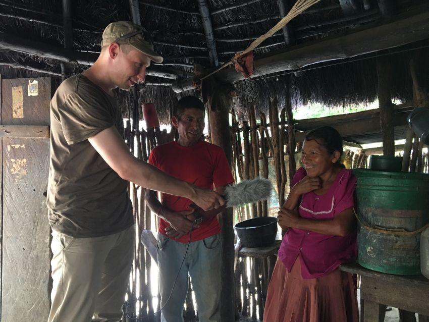 Journalist interviewt Ehepaar in einer Holzhütte in Guatemala