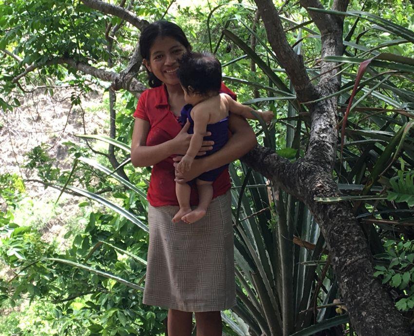 Junge Mutter mit Kleinkind auf dem Arm