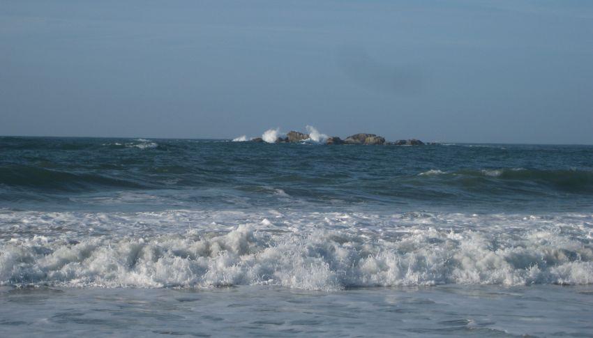 Wellen brechen sich an einem Felsen und spriten meterhoch