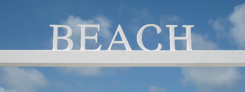 Weiße Buchstaben BEACH vor blauem Himmel in Knokke-Heist in Belgien